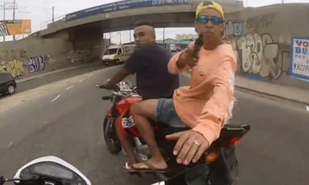 Flagrante de assalto em que o garupa aponta uma arma para outro motociclista